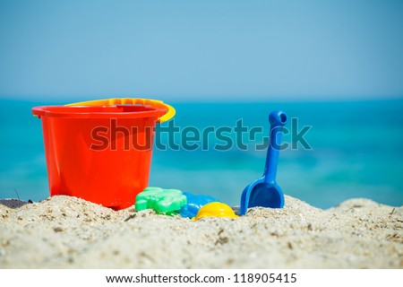 Children's beach toys - buckets, spade and shovel on sand on a sunny day - stock photo