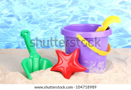 Children's beach toys on sand on water background - stock photo