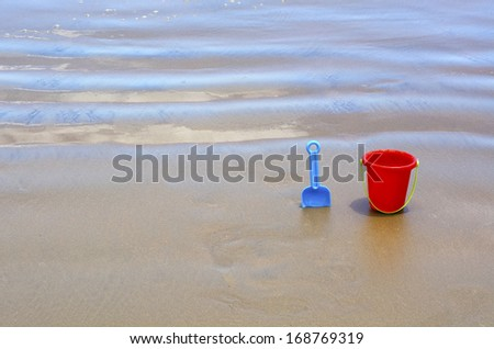 Children's beach toys, red bucket and blue spade on sand during sunny day. - stock photo