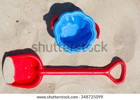 Children's beach toys - red shovel and blue bucket on sand by the sea on a sunny day.  - stock photo