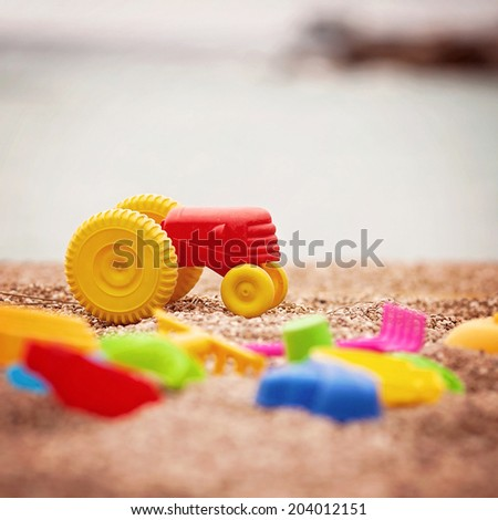 Children's beach toys - tractor, spade and shovel on sand on a sunny day - stock photo