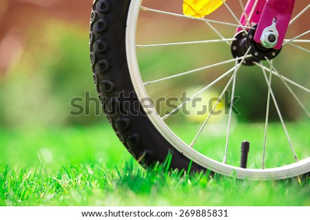 Children's bicycle on green grass, close up photo - stock photo