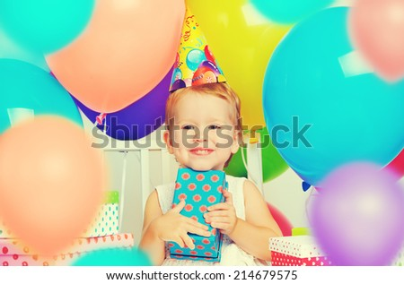 Children's birthday. happy little girl with gifts and balloons - stock photo