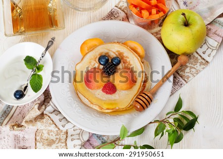 Children's breakfast lunch pancakes smiling face of the sun lion strawberry blueberry and apricot, cute food, honey, creative idea dinner - stock photo