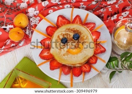 Children's breakfast pancakes smiling face of the sun strawberry blueberry and apricot, cute food, honey, creative idea lunch food idea meal dinner - stock photo