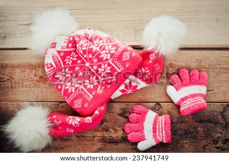 Children's cap and gloves on a wood background - stock photo