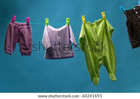 children's clothing hanging on a rope behind a blue background