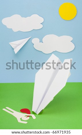 Children's collage from a paper a rough surface. The pilot lies on a  paper green grass. Wreck of the plane  concept - stock photo