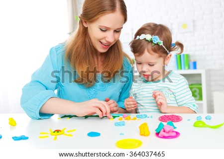 children's creativity. child with his mother sculpts from clay - stock photo
