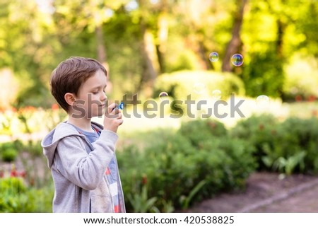 Children's Day.  Little boy blowing soap bubbles in the park - stock photo