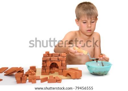 Children's designer. Child build a small house made ??of bricks - stock photo
