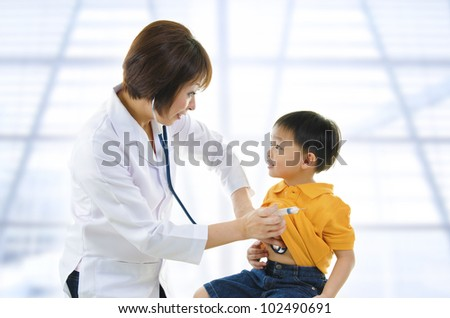 Children's doctor exams infant with stethoscope - stock photo