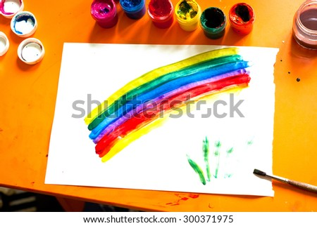 Children's drawing - rainbow and several open cans of paint - stock photo