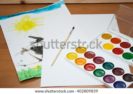 Children's drawings, a clean sheet and ink drawing with a brush on the table. Children's everyday life. - stock photo