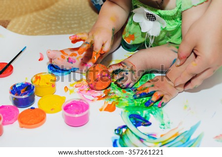 children's feet and hands in paint.children's creativity concept.drawing hands - stock photo