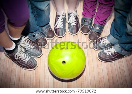 children's feet in shoes and a bowling ball for the game - stock photo
