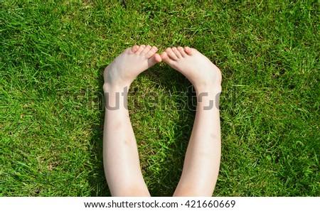 Children's feet on the green grass. - stock photo