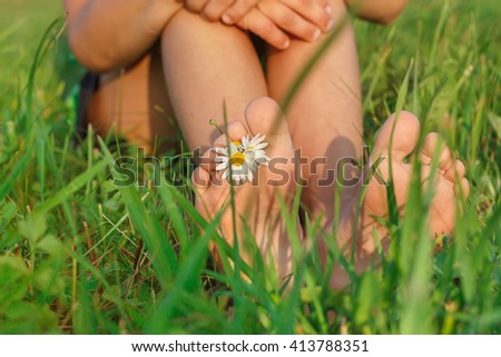 Children's feet on the green grass .People having fun outdoors in spring park - stock photo