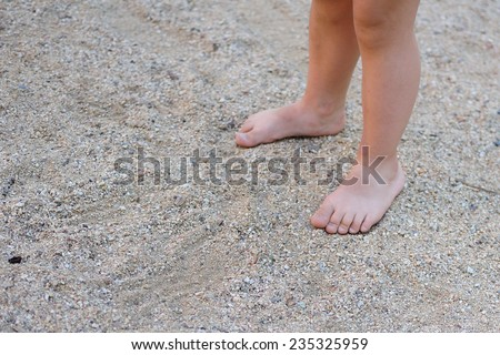 Children's foot in sand  - stock photo