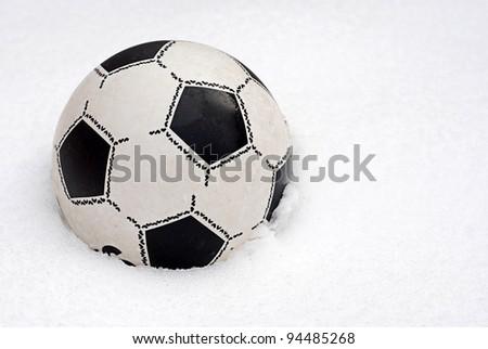 Children's football ball on the snow - stock photo