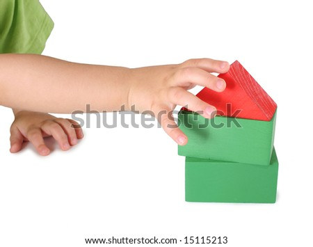 Children's hand and toy house from cubes