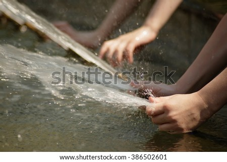 Children's hands grip the water jets in the fountain - stock photo