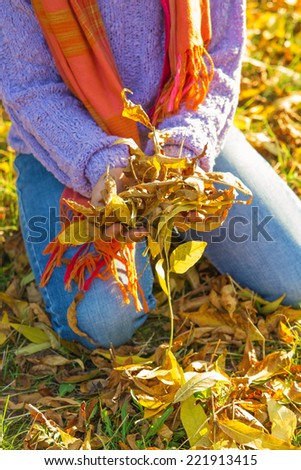 Children's hands holding a lot of autumn leaves