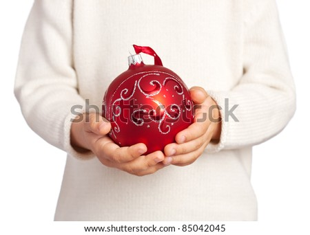 Children's hands holding a red Christmas decoration isolated on white background - stock photo