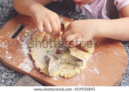 Children's hands kneading the dough for baking cookies - stock photo