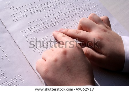 Children's hands on the book read Braille. - stock photo