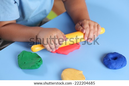 Children's hands with rolling-pin playing modeling clay. - stock photo