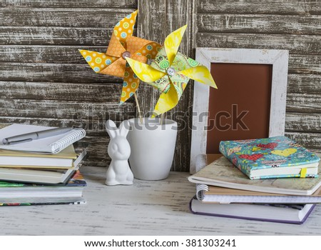 Children's home workspace with books, notebooks, notepads and handmade paper pinwheels and easter ceramic bunny. - stock photo