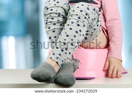 Children's legs hanging down from a chamber-pot on a blue background - stock photo
