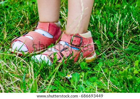 Children's legs in red sandals in green grass.
