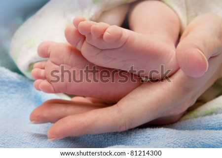 Children's legs in the palm of my mother - stock photo