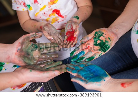 children's , men's and women's hands in the paint