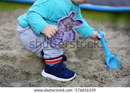 Children's outdoor play. A small child playing in a sandbox. In the hands of the baby scoop and mold for molding sand.