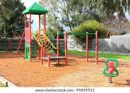 Children's playground and equipment at local park play concept - stock photo