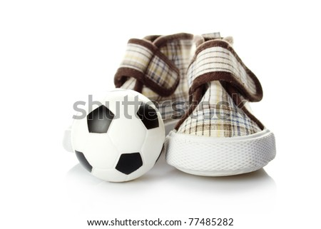 Children's shoes and a small soccer ball isolated on white background
