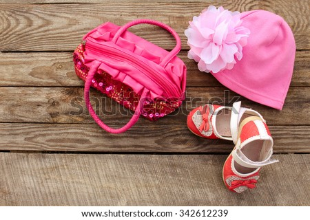 Children's shoes, hat and handbag on wooden background. Toned image.  - stock photo