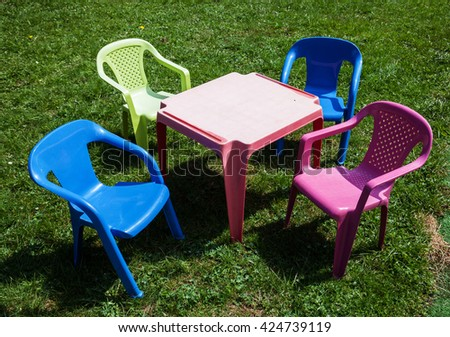 Children's small toy furniture on the grass - stock photo