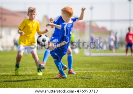 Children's soccer match. Blurred sport soccer football background. Young boys playing football match. Soccer game between blue and yellow team.