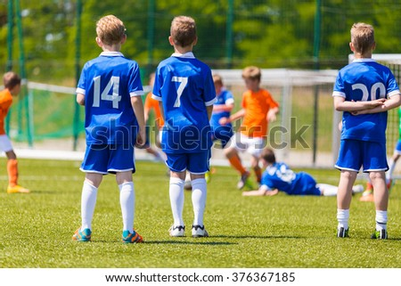 Children's Soccer Match. Kids Playing Soccer Game. Group Of Children In Soccer Team Having Training and Watching Soccer Match. Group of Boys Soccer Players Standing Together and Supporting Team. - stock photo