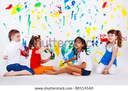 Children's team painting on the wall - stock photo