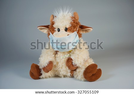 Children's toy bull in a medical mask with a thermometer on a gray background - stock photo