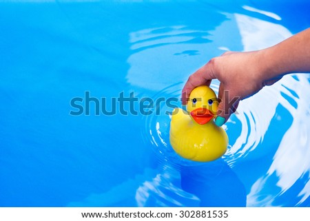 Children's toy duck drop into swimming pool - stock photo