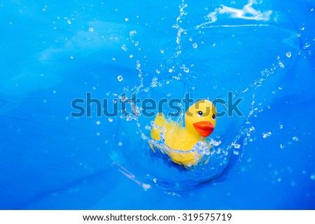 Children's toy duck drop into water with splash on blue background - stock photo