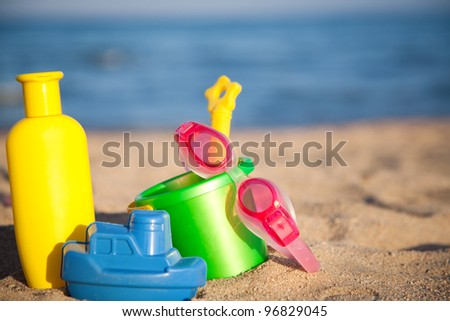 Children`s toys for sand and sunblock lotion at the beach. Summer vacations concept - stock photo
