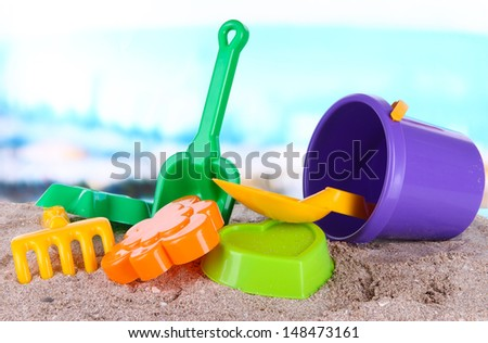 Children's toys on sand on sea background - stock photo