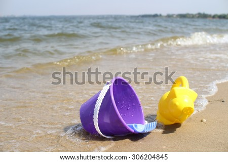 Children's toys on the beach on the river bank. Baby bucket, rake and watering can. Waves estuary. - stock photo